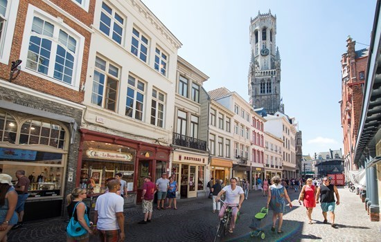 People shopping in the city center, in front of the belfry in Bruges, Belgium