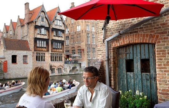Two people having diner on a terrace near the water in Bruges, Belgium
