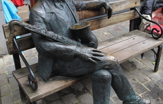 Statue of Adolphe Sax, sitting on a bench, in Dinant, Belgium
